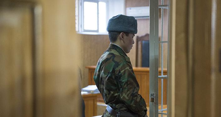 Конвоир у решетки во время судебного процесса. Архивное фото
