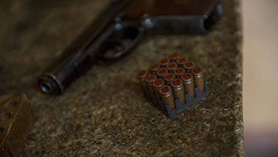 Пистолет и патроны на столе. Архивное фото