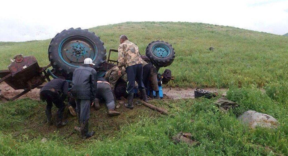 Местные жители рядом с перевернувшимся трактором в селе Кара-Сай Жамбыльской области Казахстана