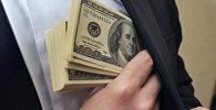Мужчина кладет доллары США в карман. Архивное фото