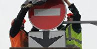 Дорожные рабочие завешивают знак, запрещающий выезд на дорогу. Архивное фото