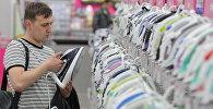 Покупатель выбирает утюг в магазине бытовой техники. Архивное фото