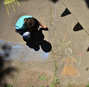 Архивное фото ребенка, который рисует на асфальте
