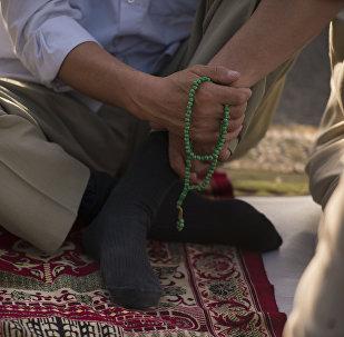 Верующий держит на руках четки. Архивное фото