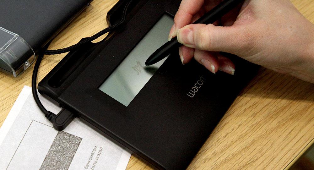 Клиент ставит электронную подпись. Архивное фото