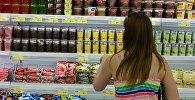Покупатель в отделе молочных продуктов гипермаркета. Архивное фото