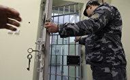 Сотрудник следственного изолятора закрывает дверь карцера. Архивное фото