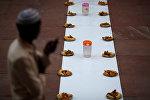 Мусульманин стоит рядом с тарелками еды перед ифтаром. Архивное фото