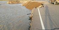 Рабочие сыпали гравий на месте размытия автотрассы в Кемине