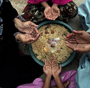 Молитва перед едой во время священного месяца Рамадан в одной из семей Карачи, Пакистан