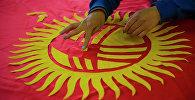 Сотрудник ГП Кыял раскладывает детали аппликации на полотно будущего флага