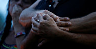 Партнеры держатся за руки после стрельбы в ночном клубе в Орландо, США.