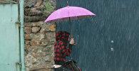 Девушка с зонтом во время ливня. Архивное фото