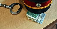 Милиция кызматкеринин фуражкасы, акча жана кишен. Архив