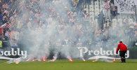 Стюард убирает ракеты с поля на фоне сектора хорватских фанатов во время матча группового этапа Чемпионата Европы по футболу — 2016 между командами Хорватии и Чехии