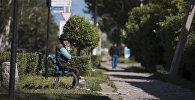 Мужчина сидит на скамейке. Архивное фото