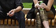 Мужчина и женщина распивают алкоголь сидя на скамейке. Архивное фото