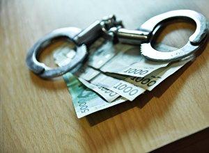Наручники с деньгами. Архивное фото