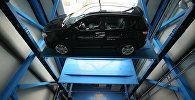 Автомобиль стоит на паллете внутри многоярусной механизированной парковки. Архивное фото