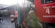 Сотрудник МЧС Кыргызстана у пожарной машины, архивное фото
