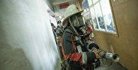 Сотрудник МЧС Кыргызстана с пожарным шлангом во время учений. Архивное фото
