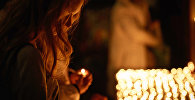 Девушка держит зажженную свечу. Архивное фото