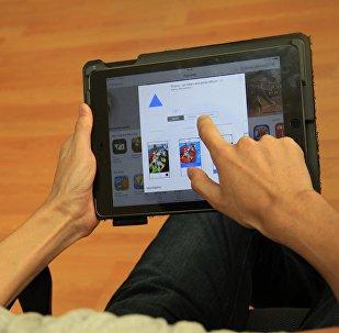 Пользователь на планшете устанавливает приложение Prisma. Архивное фото