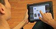 Пользователь с планшетом устанавливает приложение Prisma. Архивное фото