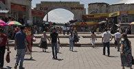 Люди у главного входа на Ошский рынок в Бишкеке. Архивное фото