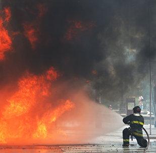 Пожарный пытается потушить пожар на автобусе. Архивное фото