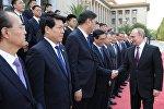 Президент России Владимир Путин (справа) во время знакомства с делегациями на церемонии официальной встречи председателем Китайской Народной Республики (КНР) Си Цзиньпином в Пекине. Архивное фото