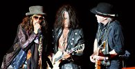 Вокалист группы Aerosmith Стивен Тайлер и музыканты группы Джо Перри и Брэд Уитфорд (слева направо) выступают на концерте. Архивное фото