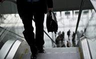 Мужчина поднимается по эскалатору. Архивное фото