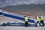 Сотрудники аэропорта устанавливают трапп для самолета в международном аэропорту в селе Тамчи. Архивное фото