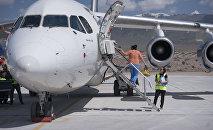 Пассажиры выходят с самолета в международном аэропорту в селе Тамчи. Архивное фото