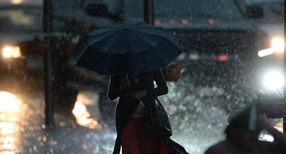 Женщина идет под зонтом во время сильного дождя. Архивное фото