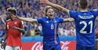Игроки сборной Исландии Биркир Бьярнасон (в центре) и Арнор Траустасон (справа) радуются забитому мячу в матче группового этапа чемпионата Европы по футболу - 2016 между сборными командами Исландии и Австрии.