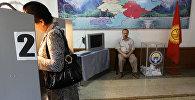 Жительница Бишкека на одном из избирательных участков города. Архивное фото