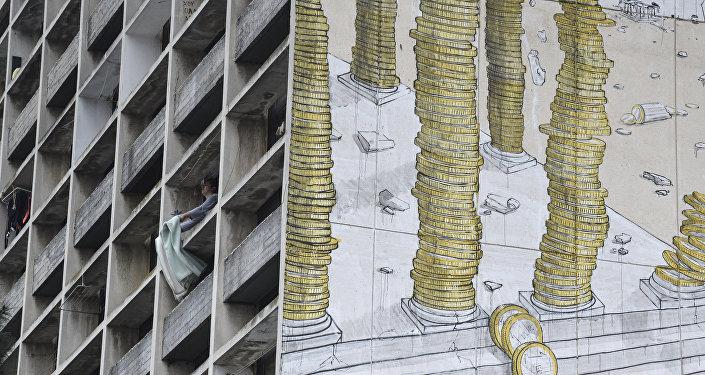 Женщина встряхивает одеяло на балконе здания. Архивное фото