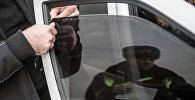 Автовладелец снимает тонировочную пленку со стекла своего автомобиля. Архивное фото