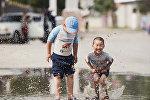 Дети играют в луже на одной из ошских улиц. Архивное фото