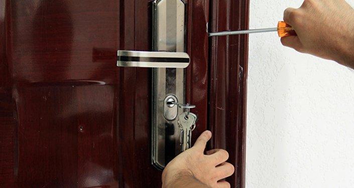 Человек пытается открыть дверь в доме. Архивное фото
