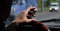 Водитель курит за рулем. Архивное фото
