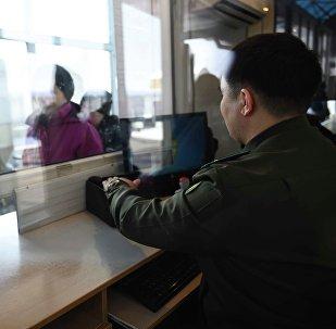 Сотрудник контрольно пропускного пункта проверяет документы у граждан. архивное фото