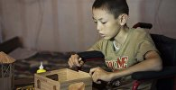 12-летний инвалид Тилек Алтымышов во время строительства домов из палочек от мороженого. Архивное фото
