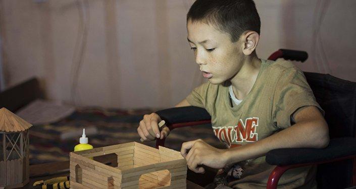 12-летний инвалид Тилек Алтымышов во время строительства домов из палочек от мороженного. Архивное фото