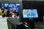 Гримеры поправляют грим телеведущим в студии. Архивное фото