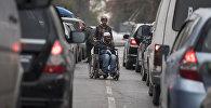 Мужчина в инвалидной коляске и женщина которые попрошайничают на одном из улиц Бишкека.