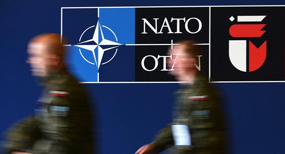 Мужчины у баннера предстоящего саммита НАТО на Национальном стадионе в Варшаве. Архивное фото