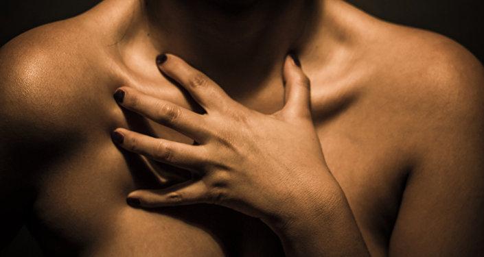 Обнаженная женщина прикрывывается руками.